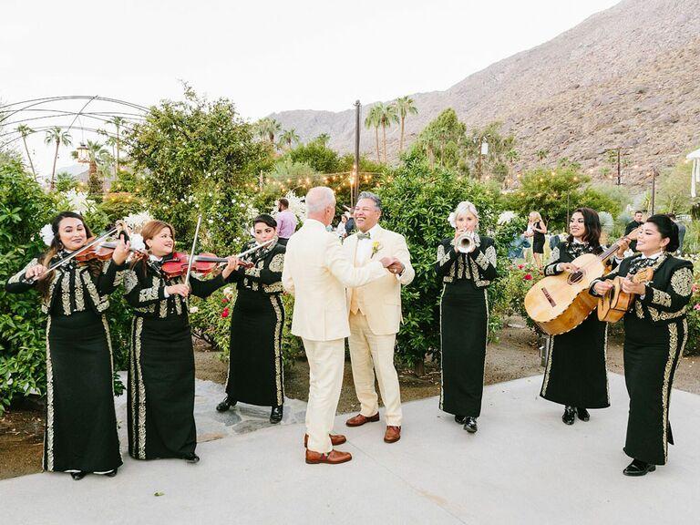 Grooms dancing to mariachi band at wedding reception