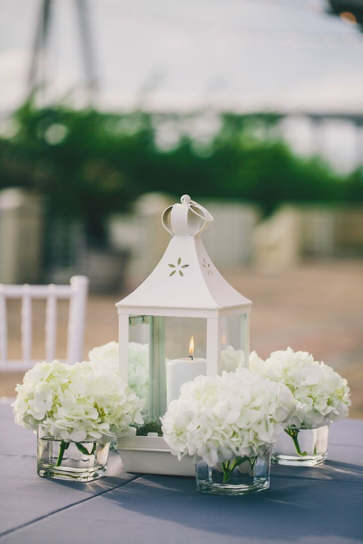 For a little romantic light, the cocktail-hour tables were topped with white lanterns filled with white pillar candles. Each lantern was surrounded by modern square glass vases filled with white hydrangeas.