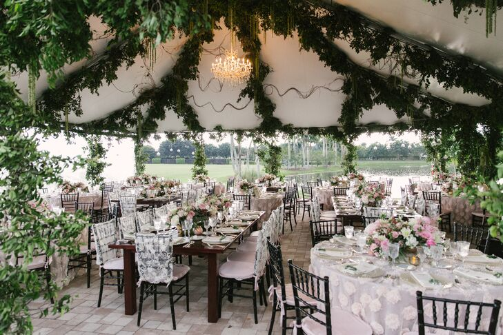 """""""One thing to note about our reception was that everything was created from scratch,"""" says Joyce. Her and Jay designed the tented reception two months before their wedding. It was decorated with chandelier lighting, mixed vintage silver chargers, grape vine and eucalyptus garlands, romantic floral centerpieces and dark chiavari chairs."""