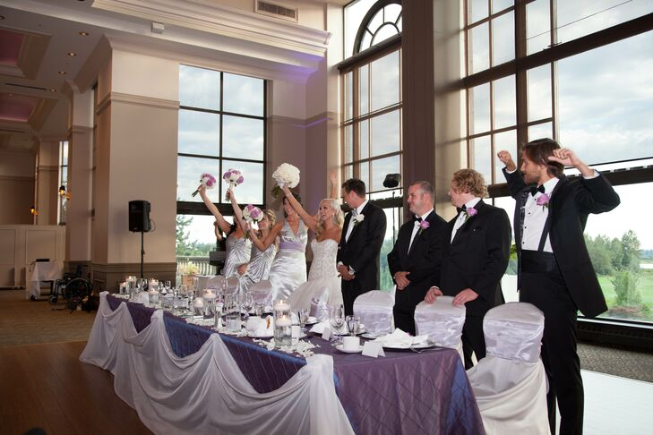 The reception took place in the ballroom at the country club. The venue features large arched windows that showcase the mountains around it. Tables at the reception were arranged with deep purple and white linens, and the chairs were tied with silver sashes.