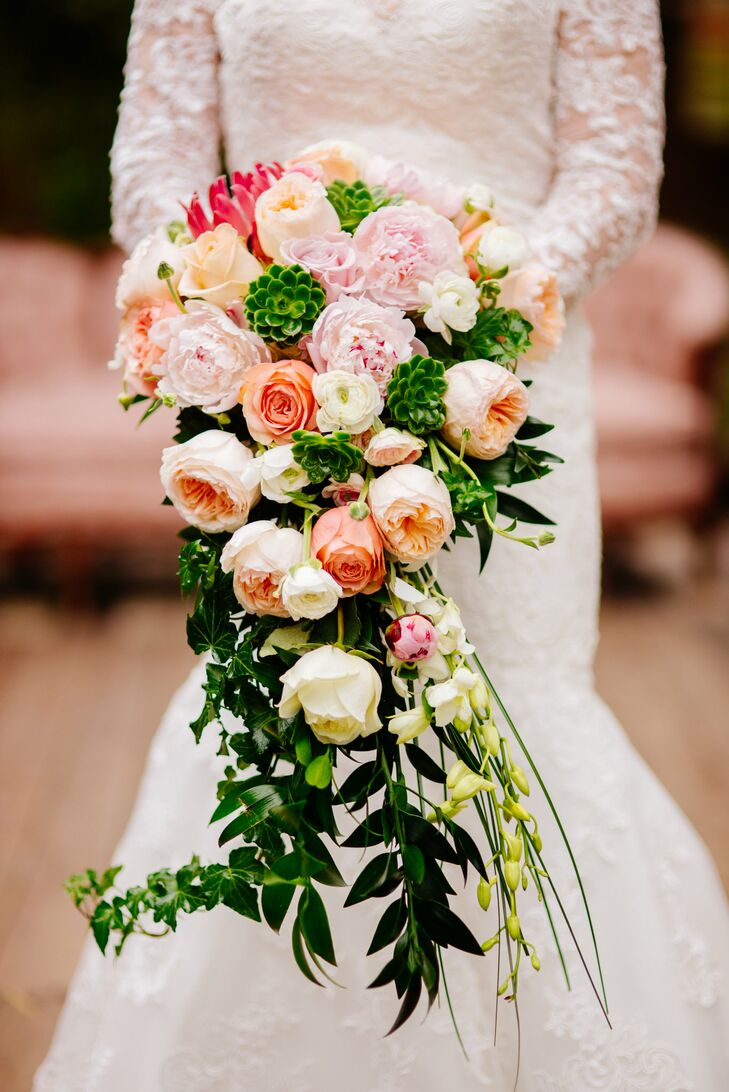 Vanessa's bouquet included a king protea with a cascading display of blush garden roses, soft coral roses, blush peonies, white ranunculus, ivy and bright green succulents.
