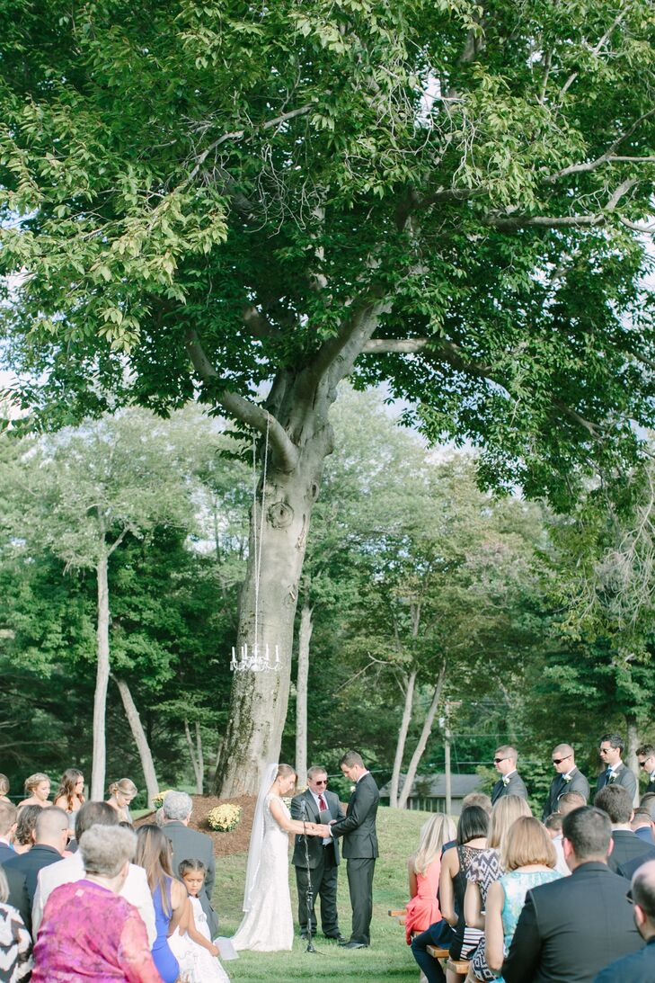 """The ceremony took place on the lawn of the Hawk's Landing Country Club, with Lynn and Joe exchanging vows under a majestic, old-growth tree. The pair hung a vintage chandelier over the spot where they said their """"I do's"""" to create a focal point at the end of the aisle, while adding an air of romance to the lush, outdoor space."""