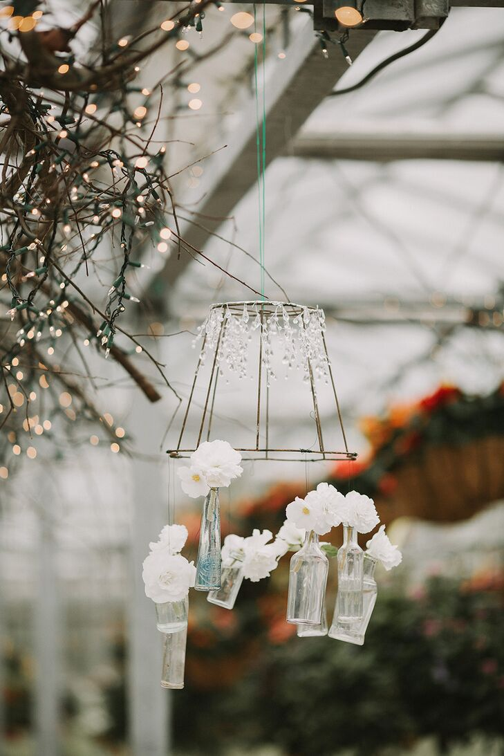 Hanging chandeliers made of metal had crystal accents elegantly draped over the top, in addition to glass bottles filled with ivory blooms dangling at the bottom.