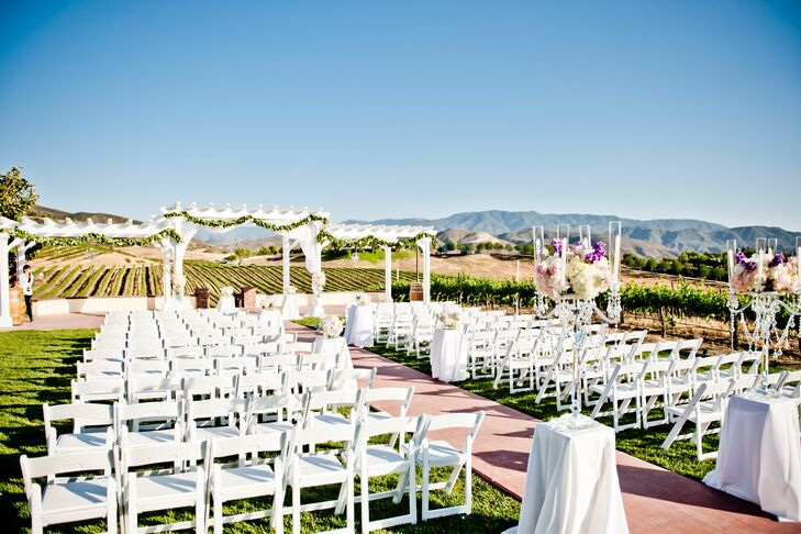 The ceremony took place on the lawn at Leoness Cellars in Temecula, California. Rows of white folding chairs were set up to face the altar, which was under the white wooden pergola that had a backdrop of the vineyards and mountains.
