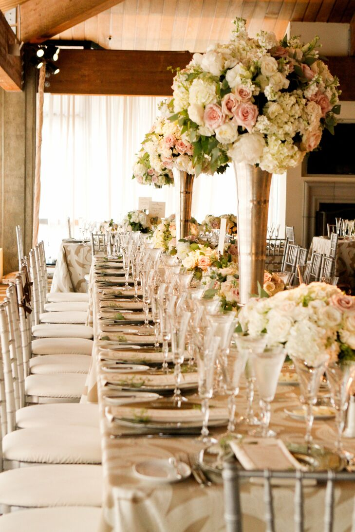 Tall arrangements of blush and ivory flowers filled tall trumpet vases and stood out from the lower, romantic florals closer to the table.