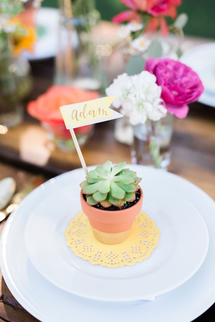 """Place cards for guests were potted succulents in hand-painted pots and little watercolored and hand-lettered flags, which were also designed to be gifts to the guests,"" Devin says."