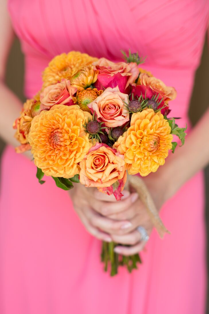 The bridesmaids held an orange round bouquet, filled with dahlias and roses (with the occasional pink flower thrown into the mix). The flower arrangement blended nicely with the bright pink floor-length bridesmaid dresses.