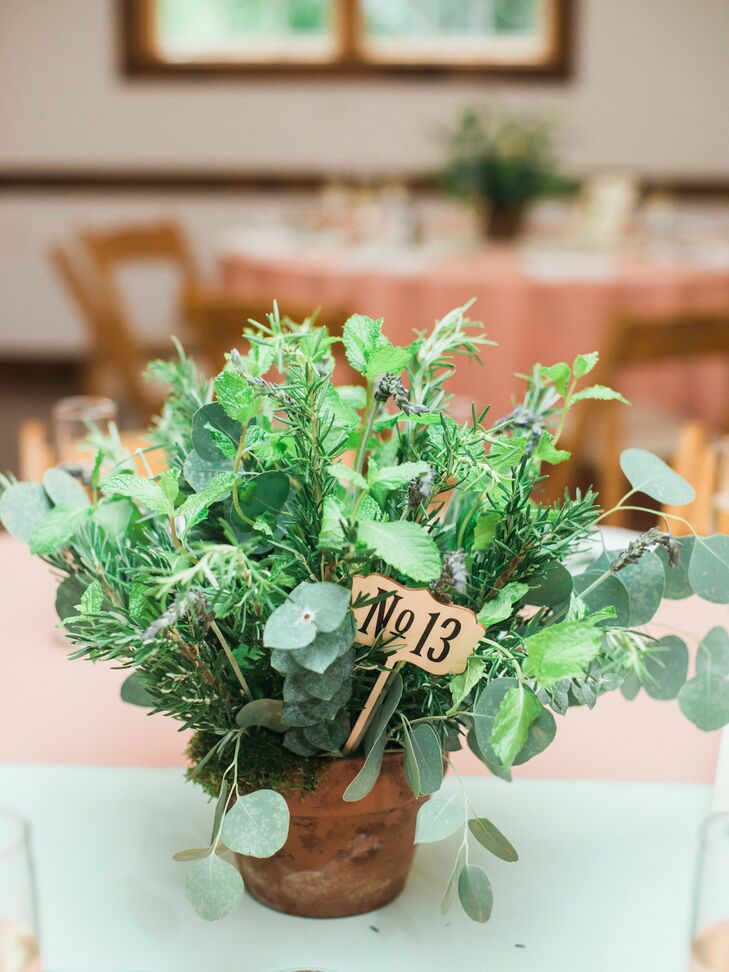 Each reception table featured a terra-cotta pot filled with rosemary, lavender, mint and eucalyptus, or white, green and pale yellow flowers with hydrangeas, roses, lisianthus, succulent blooms, hypericum berries, dusty miller and rosemary.