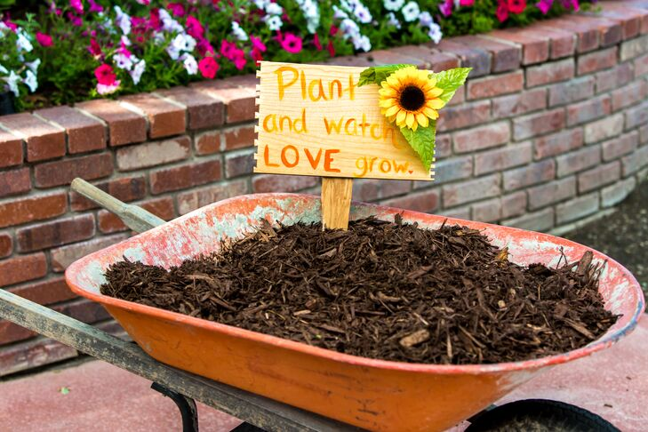 """Guests picked a packet of sunflower seeds """"growing"""" in an old red wheelbarrow filled with mulch. The wooden sign said, """"Plant and watch our love grow."""" The natural wedding favors definitely fit the rustic, outdoor theme."""