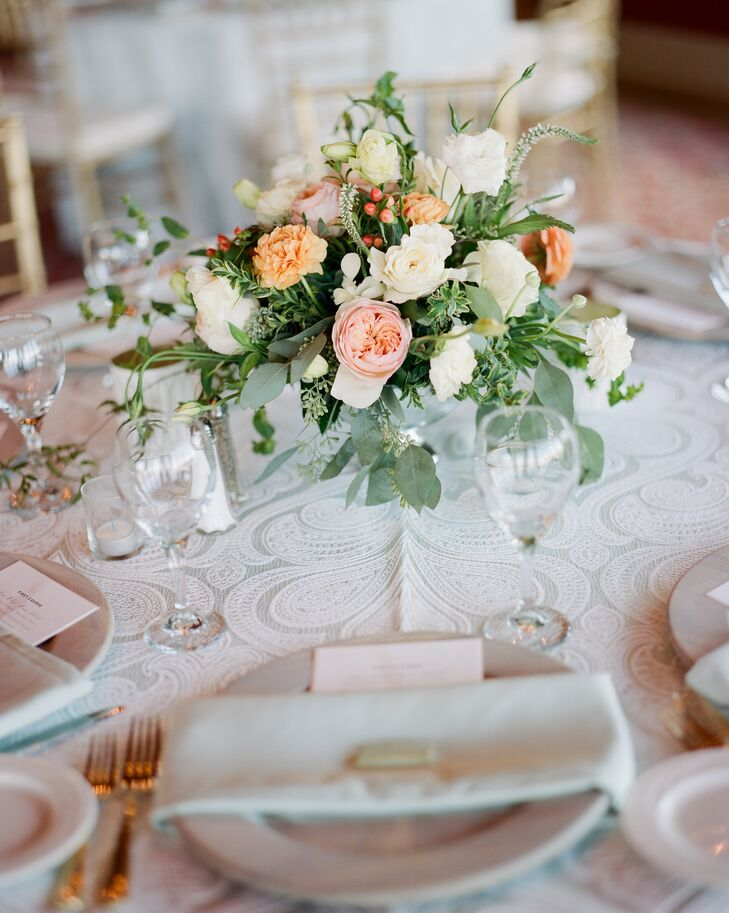The peach, pink and ivory centerpieces were made with garden roses, eucalyptus and smilax.