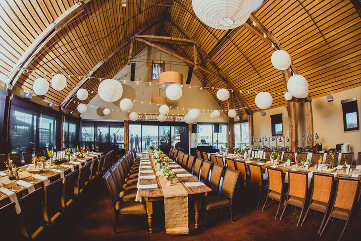 The reception was held inside the barn at Brasada Ranch. White paper lanterns hung above long wood dining tables with brown draped table runners.