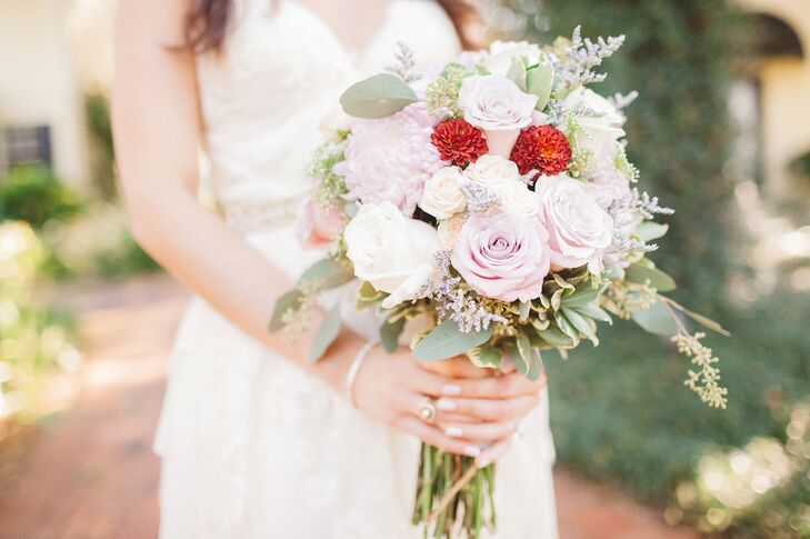 Alta Fleura arranged blush and cream roses, Queen Anne's lace, seeded eucalyptus as well as blush and red dahlias into a bouquet wrapped with champagne ribbon for Nikole. The romantic arrangement was chosen to complement her enchanted garden fairy tale vision for the wedding.