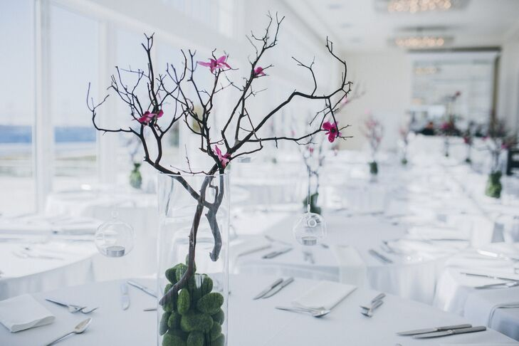 Tall vases with branches, moss balls, hanging candles and orchids offset the tall ceiling of the reception space.