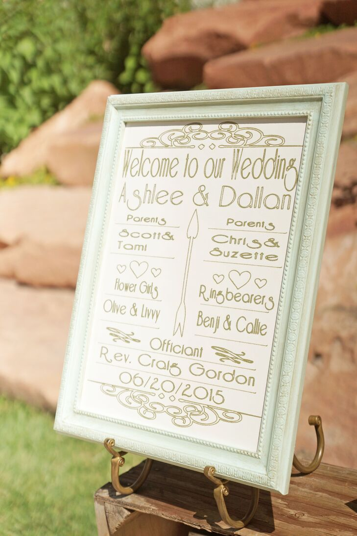 Ashlee and Dallan honored their parents, flower girls and ring bearers with a whimsical wedding sign in a mint frame, decorated with gold hearts and arrows.