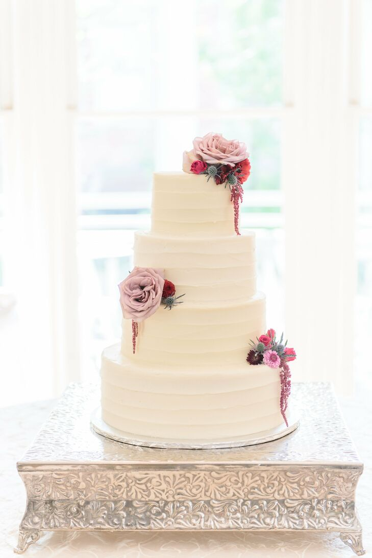 The newlyweds served a four-tier cake with layers of red velvet and cream cheese icing and vanilla cake with buttercream icing, which was topped with purple and red blooms.