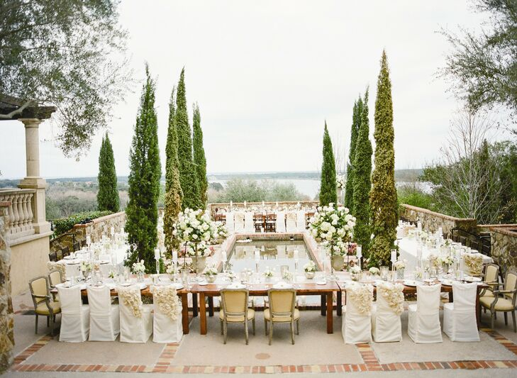 Cyprus trees and sweeping views of the water gave the reception a Tuscan-inspired feel. The long farm tables were arranged around a long reflecting pool that would enhance the romantic ambiance of the space as the sun began to set.