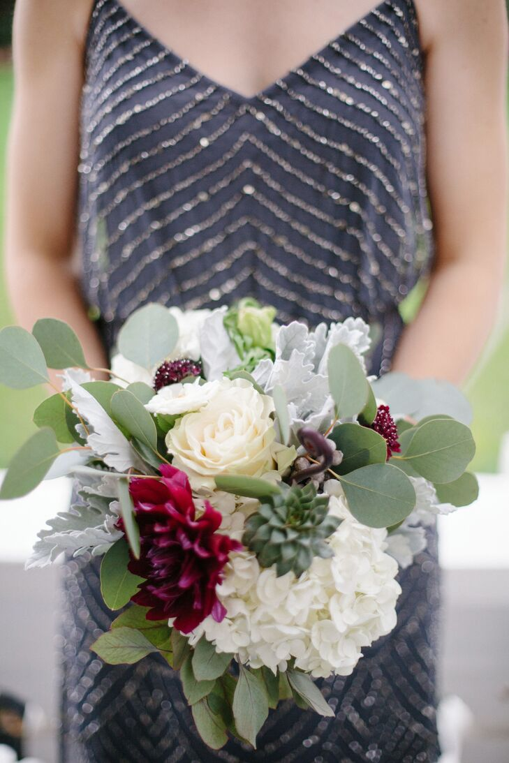 """I love succulents. I love the diverse colors and shapes and how resilient they are, so I wanted them to be a big part of our flowers,"" Miriam says. To bring out the dusty blue of the succulents, silver dollar eucalyptus, silver brunia and blue privet berries were added to the bouquets. The whimsical bridal bouquet also included plum dahlias, black scabiosa and fiddleheads."