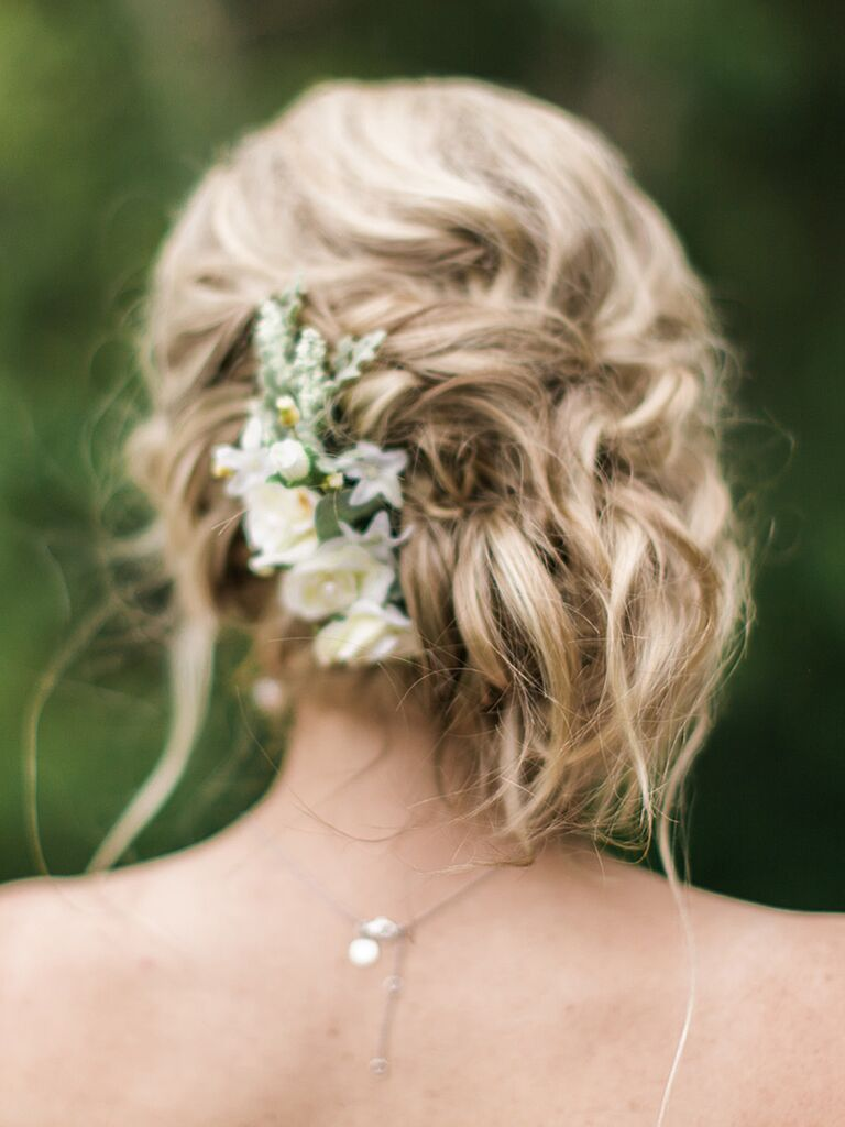 Adding flowers to a messy side swept bun creates a simple and elegant chignon