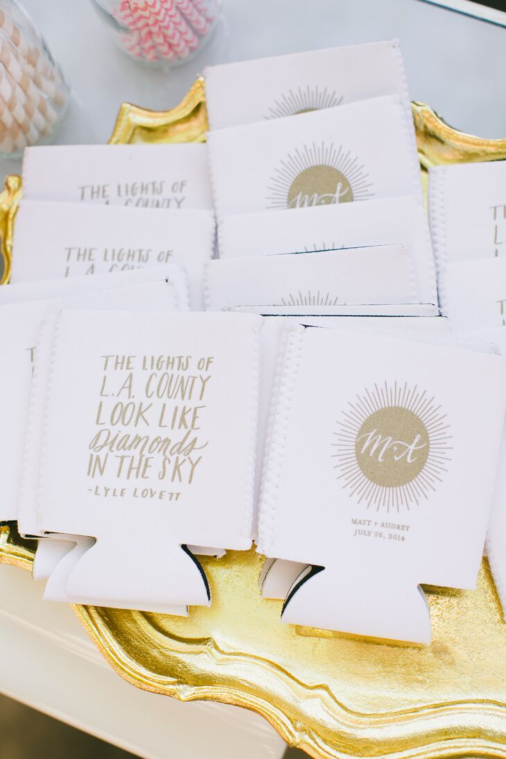 """Guests received white and gold koozies, with the couple's initials on one side and lyrics on the other from """"LA County"""" by Lyle Lovett."""