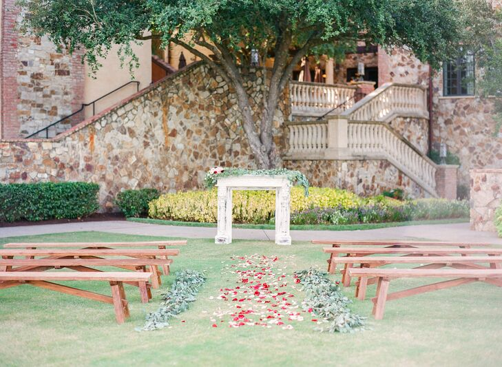 "Michelle and Michael had an intimate outdoor ceremony complementing the venue's natural greenery. They decorated with simple wooden benches, a white vintage mantle as well as garden roses, rose petals and eucalyptus. ""I chose the tree as a backdrop of the ceremony, because I love how the green of the leaves photographs,"" says Michelle."