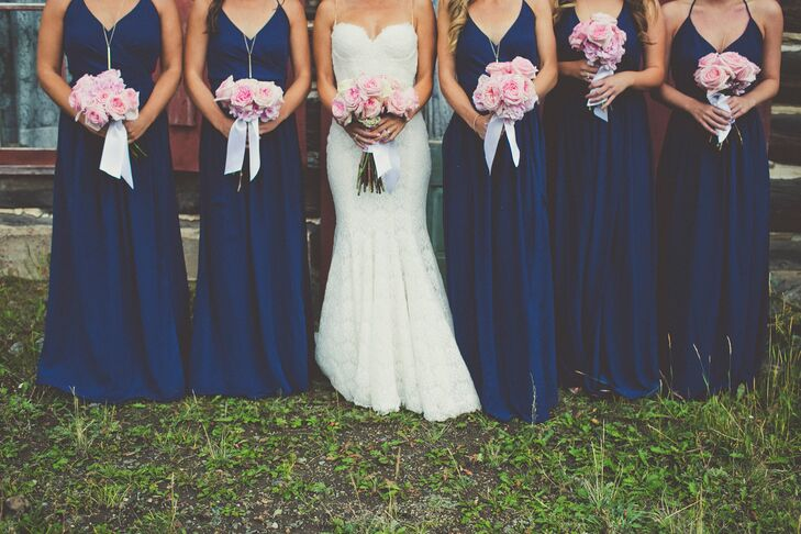 The bridesmaids wore floor-length navy Joanna August dresses with long gold necklaces and nude heels.