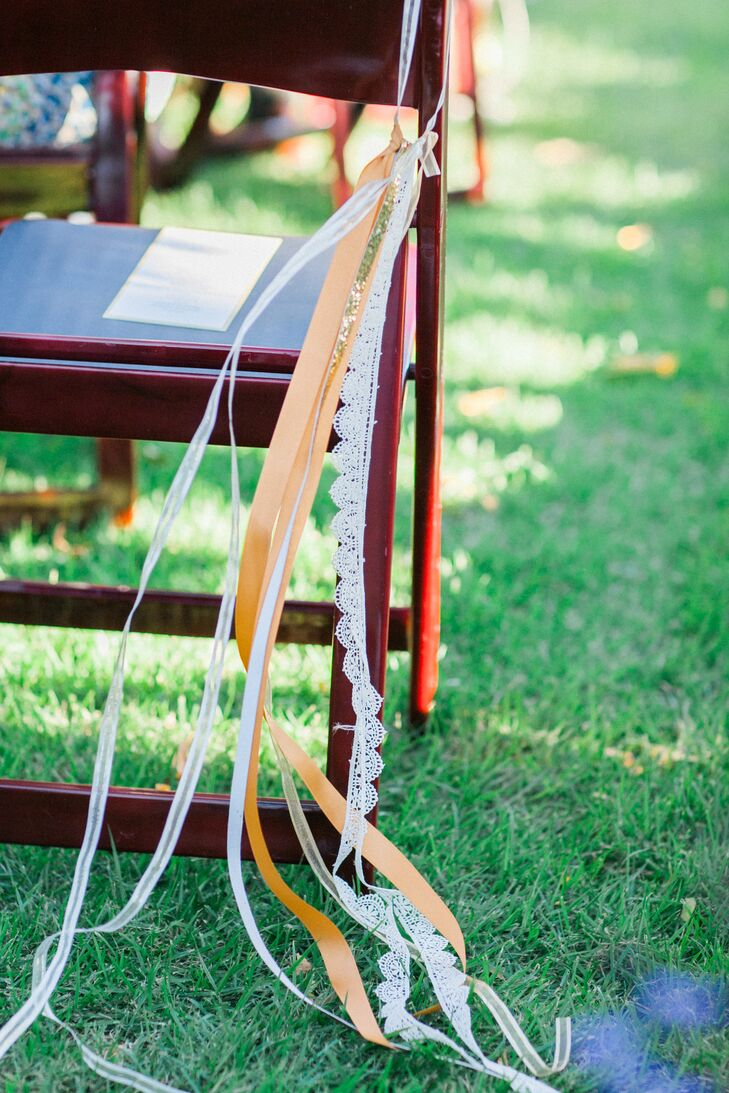 The aisle chairs were adorned with bunches of gold and lace ribbons that blew in the wind.