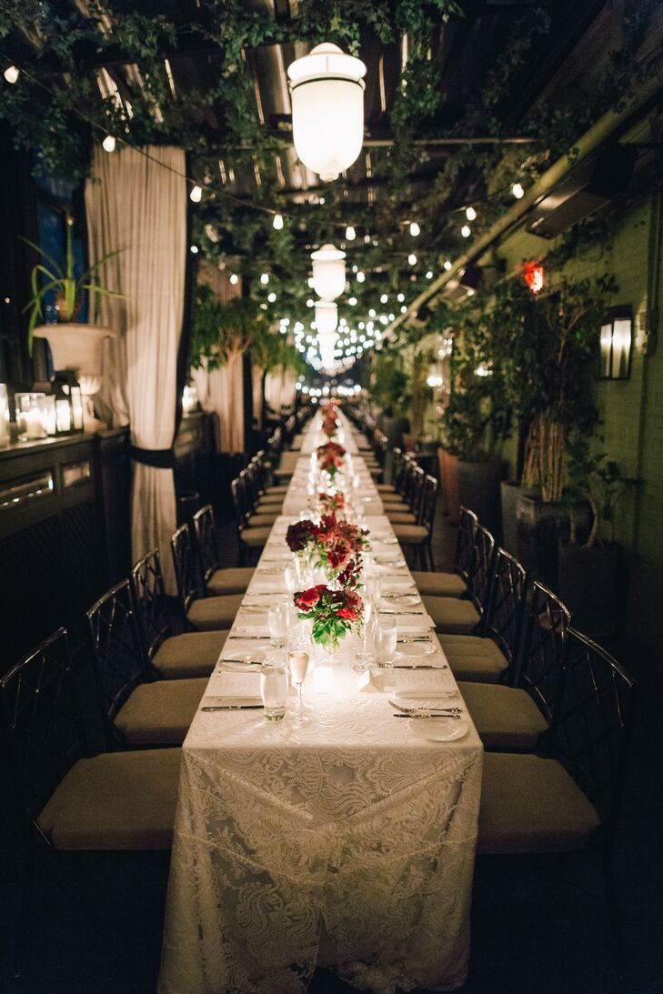 The reception also took place on the Gramercy Park Hotel's rooftop. Long banquet tables stood beneath a canopy of ivy and bistro lights, dotted with bouquets of burgundy florals and flickering candlelight. As guests dined on fresh, seasonal eats, they took in the twinkling lights of the New York City skyline.