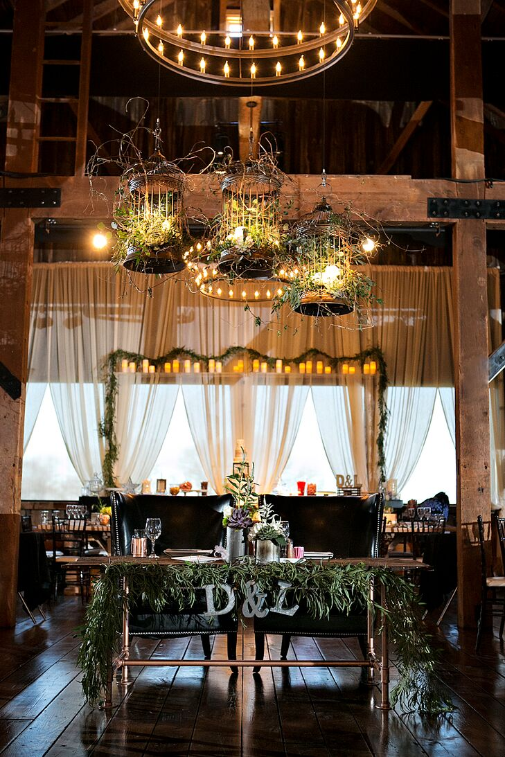 """Representing their juxtaposing backgrounds and personalities, David and Lee picked out a custom sweetheart table for their reception at the Farm at Eagles Ridge in Lancaster, Pennsylvania. A eucalyptus garland covered the front of their wooden seating, while silver marquees of their initials accented the center. Three rustic birdcages filled with greenery, curly willow tips and candlelight also hung overhead. """"It was important to pull in as many types of metals, woods and textiles to help tell a design story of our love,"""" David says."""