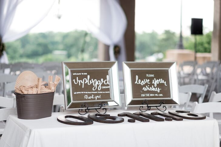 "A DIY guest book included a wooden cutout of ""06.11.16"" for guests to sign before the ceremony. There were also wooden fans and water bottles set out for guests. ""Of course, it just happened to be the hottest day of the year for our outdoor ceremony,"" Amanda says."