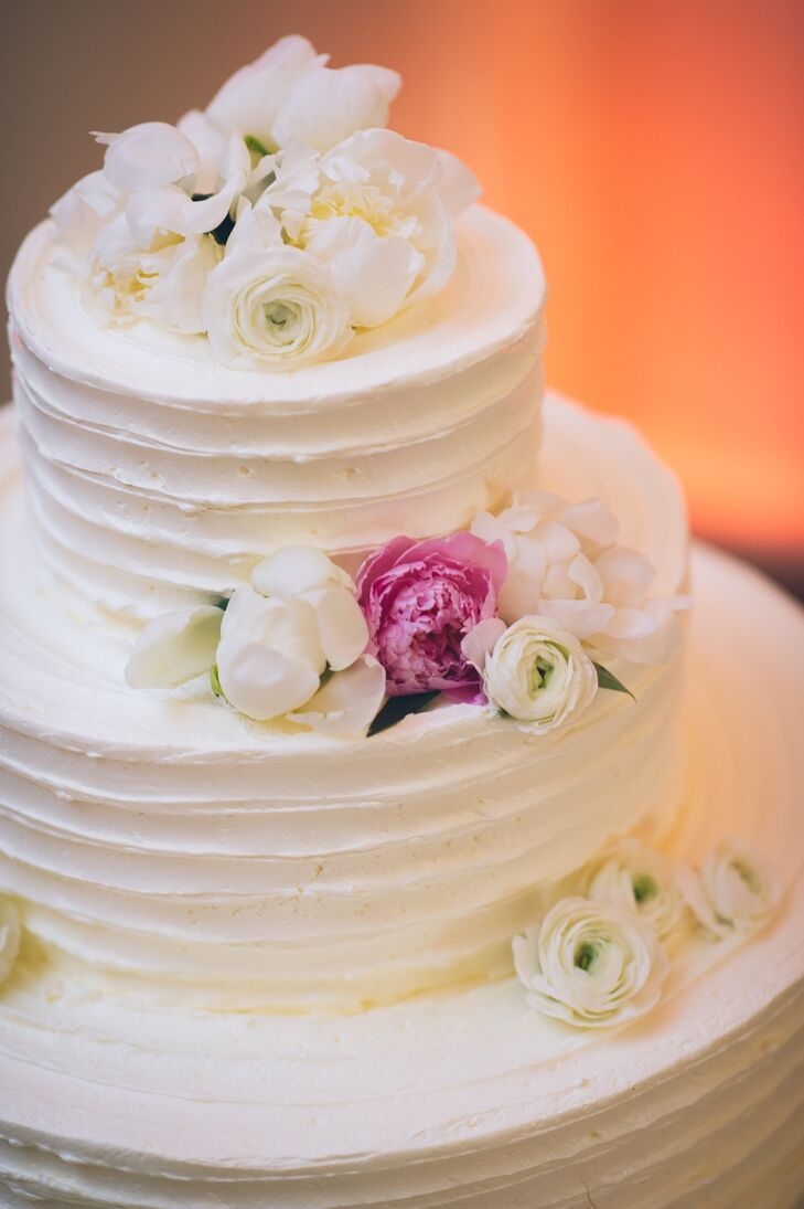 Every layer of their wedding cake corresponded with the couple's romantic centerpieces. Creative Cakes By Donna covered each round tier with white buttercream frosting below fresh flowers. White and pink peonies as well as white ranunculus and slight green leaves peaked out of either side or a natural design.