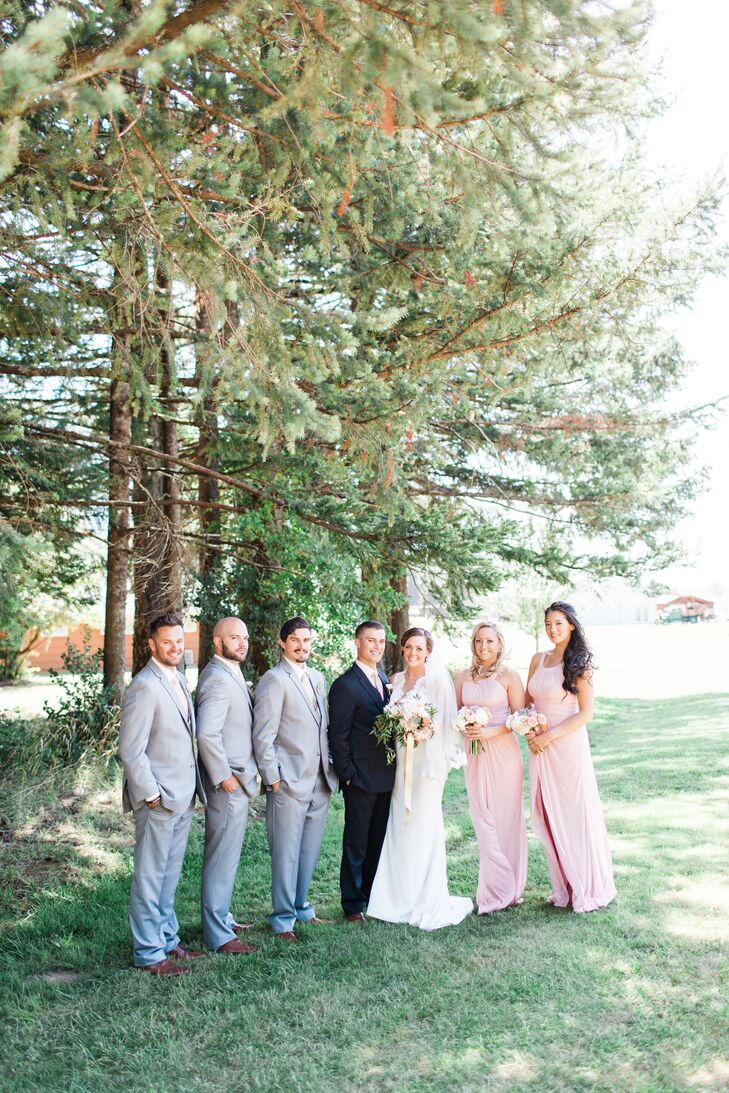 """Since it was a summer wedding, we had already decided on light pink and white florals, and it was important to us that everything had a cohesive look, so my bridesmaids wore pink BHLDN dresses, while Jake and the groomsmen wore matching ties,"" Eliza says. ""We thought gray suites would be best for our outdoor summer wedding, so we opted for light gray groomsmen suits, while Jake wore dark gray."""