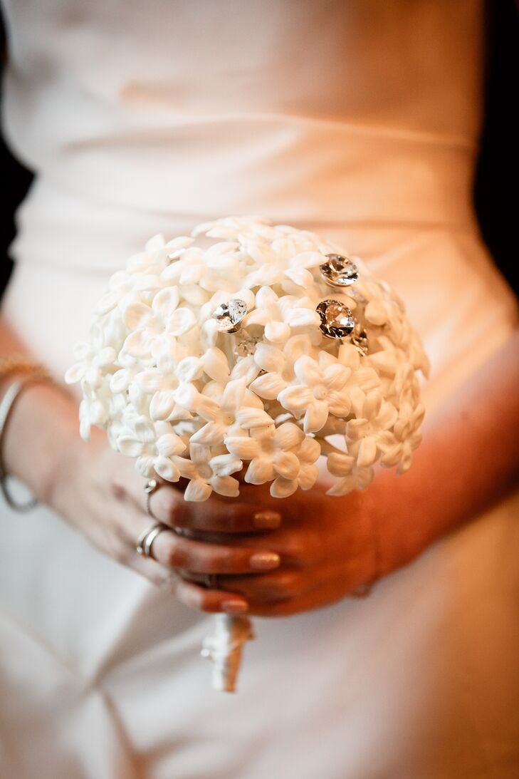 For the ceremony, Allison and Jason opted for paper florals that would offer a unique spin on their Parisian flower shop theme. Instead of carrying a bundle of fresh white blooms down the aisle, Allison's petite bouquet was filled with paper tube roses dotted with glam crystal accents.