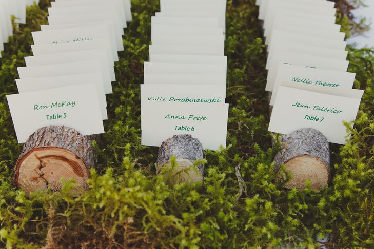 The white escort cards were tucked into tree slices and were displayed in a bed of fresh greenery, adding to the natural theme of the wedding.