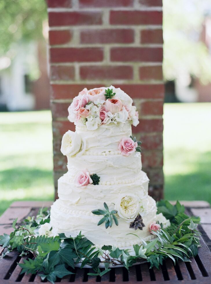 """With a few Pinterest pictures as inspiration, Hopkins Eatery took care of their buttercream wedding cake design. The confection matched their theme with garden roses, roses, succulents and hydrangeas on every tier as well as the topper. The base was even circled with greenery. Below its frosting, the cake also had a personalized detail. """"We both love traditional yellow cake with buttercream frosting, so picking out the flavors was easy,"""" Laurie says."""