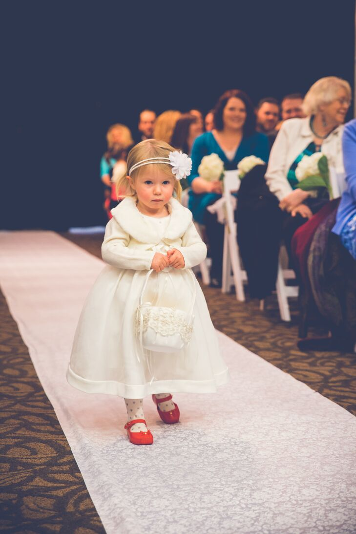 The flower girl walked down the aisle during the ceremony, holding her white basket that matched her ivory long-sleeved dress accented with fur. She wore a headband embellished with a single flower and wore bright red shoes, giving the outfit a pop of color.
