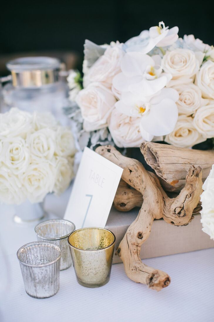 Table settings were made with driftwood, sea glass, candles and white roses.