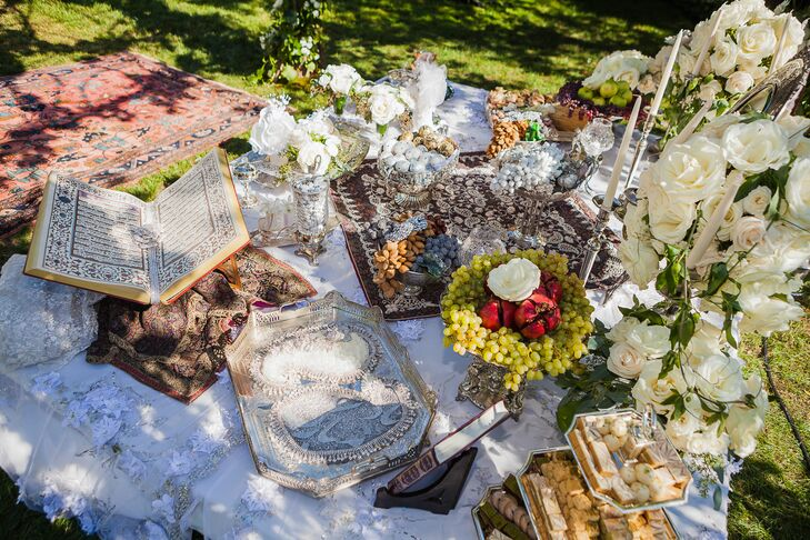 "A traditional sofreh aghd was placed under Simin and Nicholas's chuppah for the Persian portion of their ceremony. The spread featured items that symbolized the couple's new life together, including mirrors and candles for light and purity, pastries for the sweetness of life, eggs and nuts for fertility, coins for wealth and prosperity, pomegranates for a joyous future and incense to guard against misfortune. ""The Persian ceremony was joyous, playful and interactive,"" Simin says. ""Keeping with tradition, when my uncle asked me if I would accept Nicholas to be my husband, I did not answer right away, coyly pretending to be unsure. Guests called out excuses for my silence, also a typical custom at Persian weddings. At the same time, women from my family held a cloth over us, taking turns rubbing kalleh ghand [sugar cones] to sweeten the union.  Once asked three times, I accepted."""