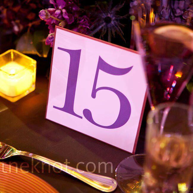 Dark purple block numbers resting next to purple centerpieces marked the tables.