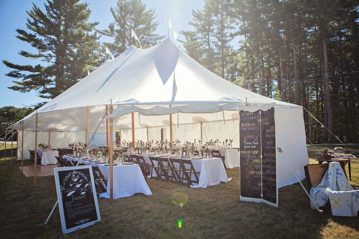 Long banquet tables were set up under a sailcloth tent for an intimate wedding reception venue.