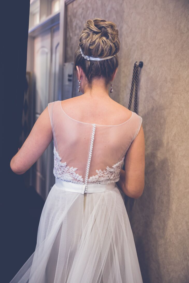 Kyra wore an ivory wedding dress with an illusion neckline, which buttoned up from the back. The bodice was intricately decorated on the front and had a tulle skirt. She wore her hair in an updo bun, which had an ivory headband wrapped about it.