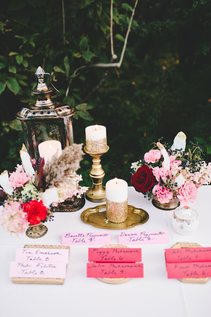 Pink escort cards waited at a table decorated with found objects in metallic colors.