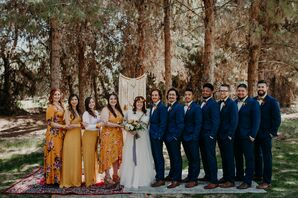 Wedding Party Wearing Mismatched Orange Dresses and Complementary Navy Suits