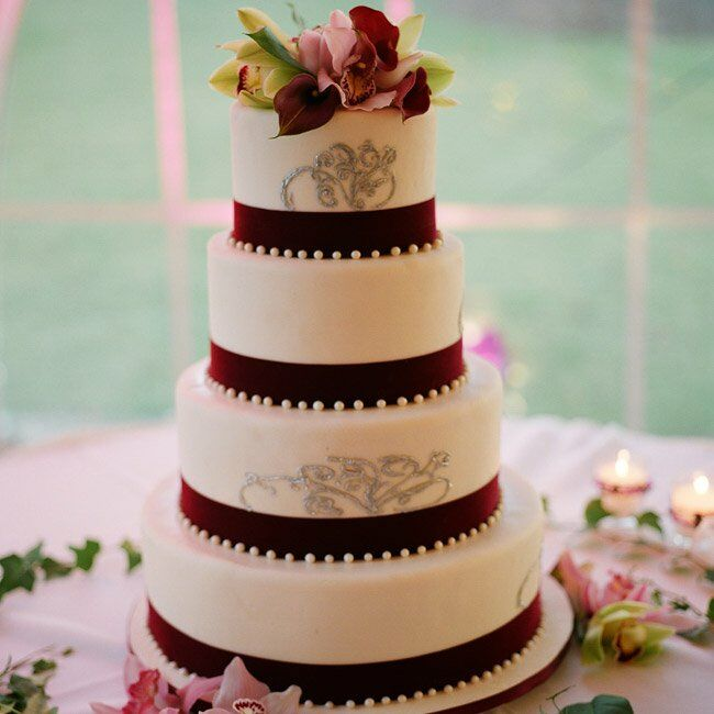 Plum ribbons and pearls surrounded each tier of the cake. Fresh flowers at the top and base and the couple's signature swirl motif further personalized the rich confection.