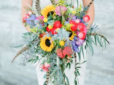 Unique bridal bouquet with bright blooms and feathers