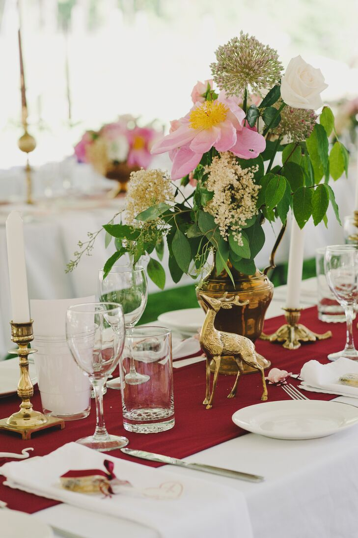 The farmhouse style dining tables were covered in burgundy runners and decorated with antique gold pieces, like deer figurines. The gold vases were filled with pink peonies, white roses and allium.