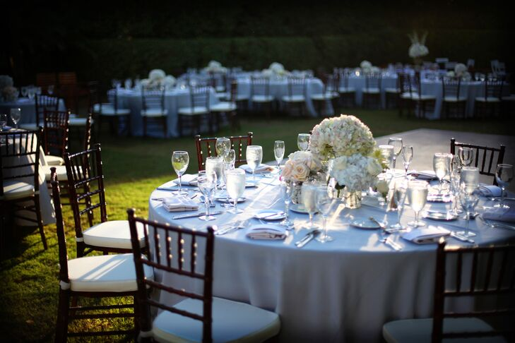 The couple decorated their reception with white linens, dark chiavari chairs, white cushions, and clear glass stemware. Each table was given a three-piece centerpiece of white hydrangea, peach roses and ivory hydrangea.