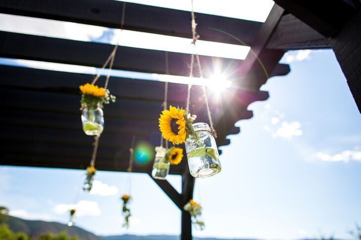 Embracing their sunflower-filled theme, Kerry and Billy hung sunflowers in mason jars from their pergola at the ceremony. The staggered hanging flowers definitely added romance to the outdoor ceremony at Crooked Willow Farms in Larkspur, Colorado.