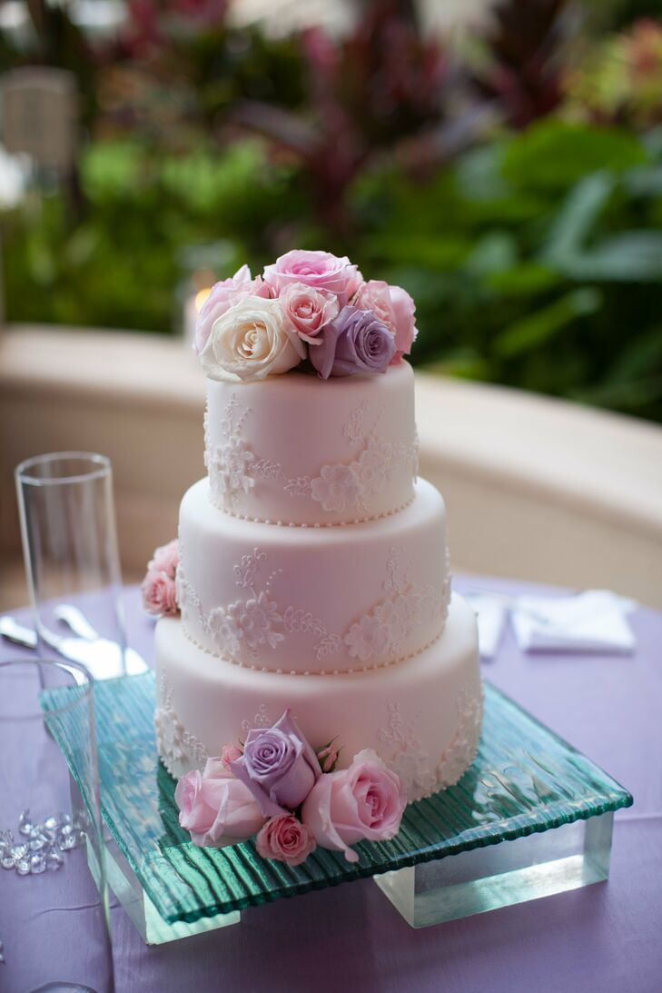 The couple chose a three-tiered white cake accented with a lace-inspired floral design and topped with fresh roses.