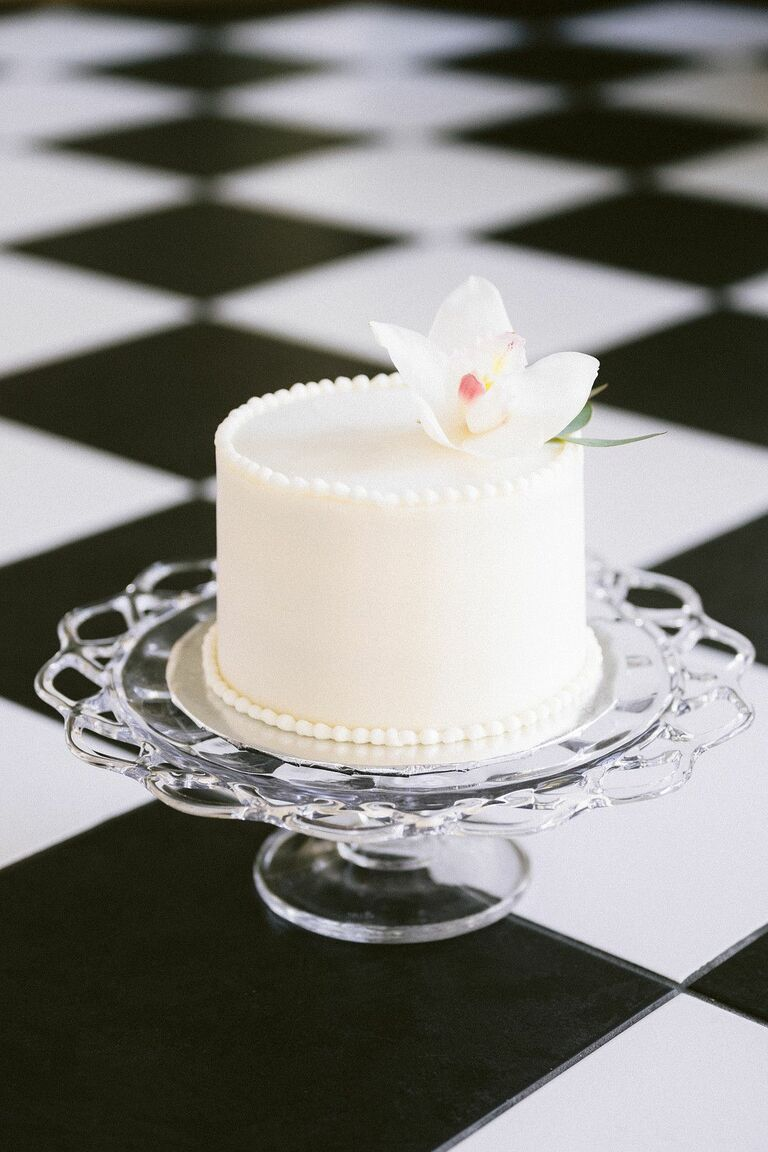 Simple one-tier white wedding cake on glass cake stand