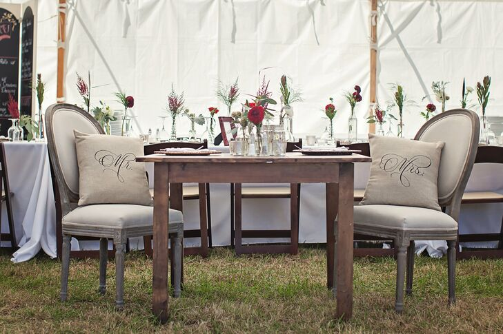 At the reception, the bride and groom sat at a rustic wooden table decorated with glass jar centerpieces. Their vintage styled chairs were adorned with canvas Mr. and Mrs. pillows.